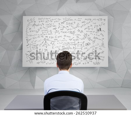 student man looking to desk with athematics equations and formulas - stock photo