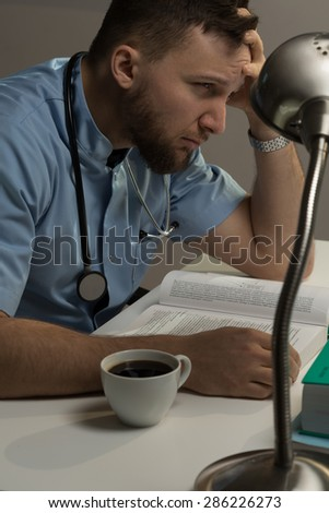 Student of medicine is studying for his exams - stock photo