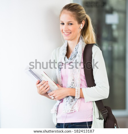 Student on campus - pretty, female student with books and laptop during her school day on campus school library (color toned; shallow DOF) - stock photo