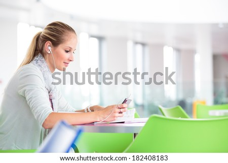 Student on campus - pretty, female student with books and laptop wokring/studying during her school day on campus (color toned image, shallow DOF) - stock photo