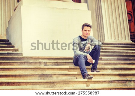 Student on Campus. Wearing gray V neck cardigan sweater, blue pants, brown sneaker, wristwatch, holding mobile phone, a young guy sitting on stairs outside office building, smiling, looking at you. - stock photo