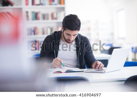 student preparing exam and learning lessons in school library, making research on laptop and browse internet - stock photo