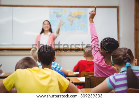 Student raising hand to ask a question at the elementary school - stock photo
