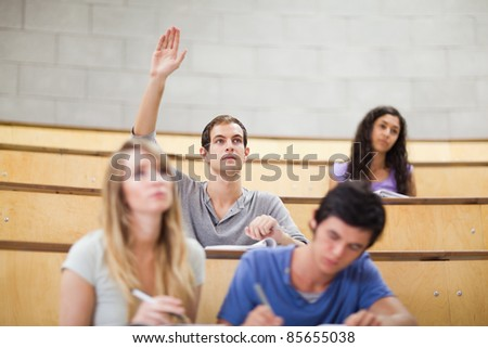 Student raising his hand while his classmates are taking notes in an amphitheater - stock photo
