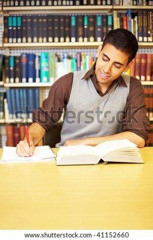 Student reading a book and taking notes - stock photo