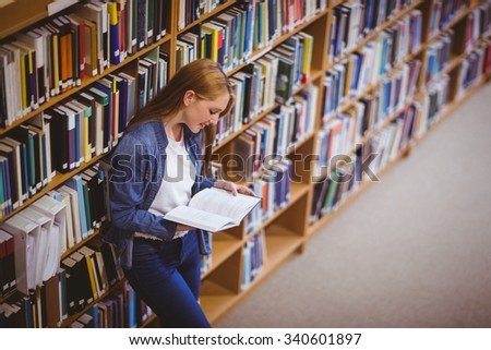 Student reading book in library leaning against bookshelves at the university - stock photo