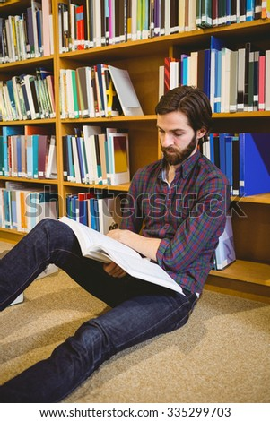 Student reading book in library on floor at the university - stock photo