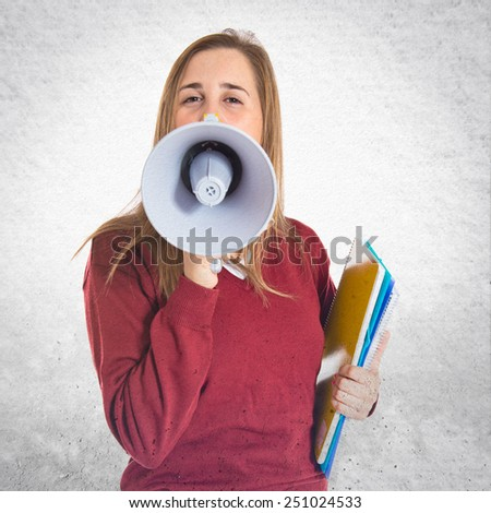 Student shouting by megaphone over textured background  - stock photo