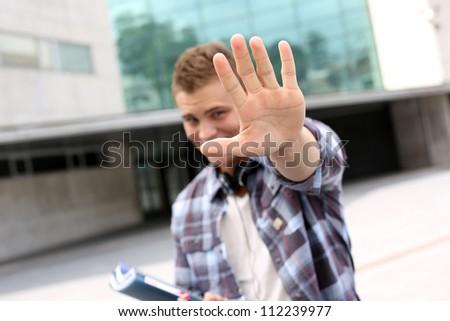 Student showing hand towards camera - stock photo