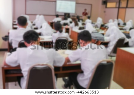 student sitting in a lecture room with the teacher front of  class and  projector slide screen Blur blurred  background  view from back  - stock photo