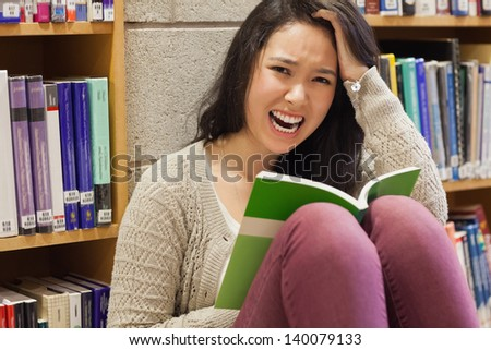 Student sitting in the floor in a library and holding a book while being stressed - stock photo