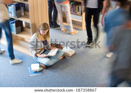 Student sitting on floor in library classmates walking blur motion - stock photo