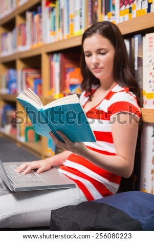 Student sitting on floor in library reading at the university - stock photo