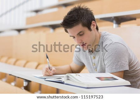 Student sitting reading a book and taking notes in lecture hall - stock photo