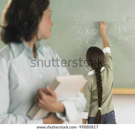 Student solving arithmetic on the chalkboard - stock photo