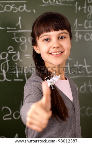 student standing near the green board - stock photo
