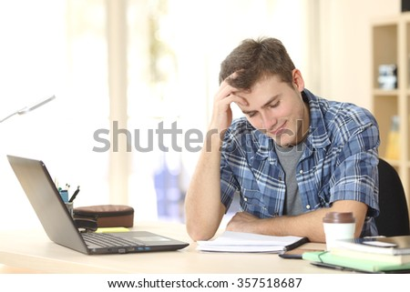 Student studying and learning reading notes on a desktop in his room at home - stock photo