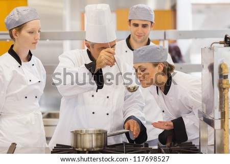 Student tasting the teacher's soup in culinary school - stock photo