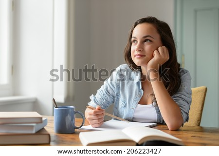 Student teenage girl studying at home daydreaming looking away - stock photo