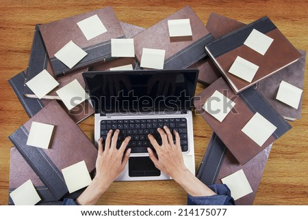 Student typing with laptop around books and sticky notes - stock photo