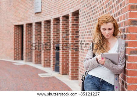 Student using a tablet computer outside a building - stock photo