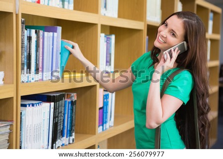Student using her phone in library at the university - stock photo