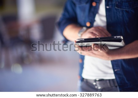 student using tablet computer for education in school, university interior in background - stock photo
