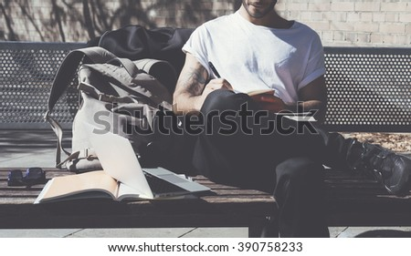 Student wearing white tshirt sitting city park and writes message. Studying at the University, working project. Books, generic design laptop, backpack bench. Wide - stock photo
