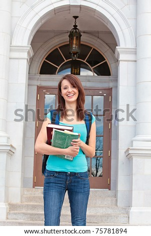 Student with books on campus - stock photo