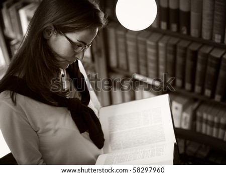 Student with glasses standing at bookshelf in old university library reading a book, sepia toned. - stock photo