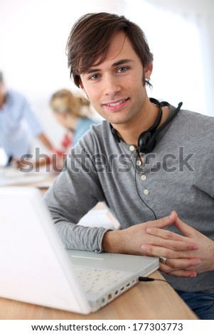 Student with headset on doing English language test - stock photo