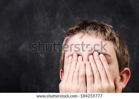 Student with his hands over his face  - stock photo