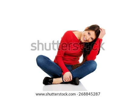 Student woman sitting cross legged on the floor. - stock photo