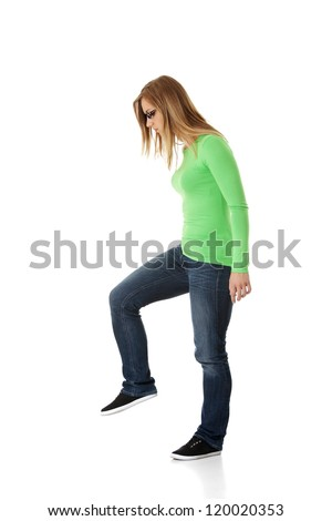 Student woman trying to trample something, isolated on white - stock photo