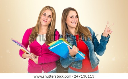Student women doing victory gesture over ocher background - stock photo