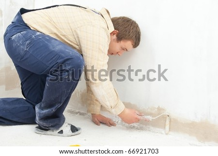 student worker paint wall with small roller - stock photo