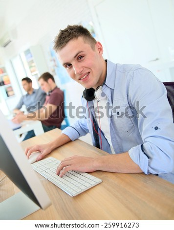 Student working on computer in class - stock photo