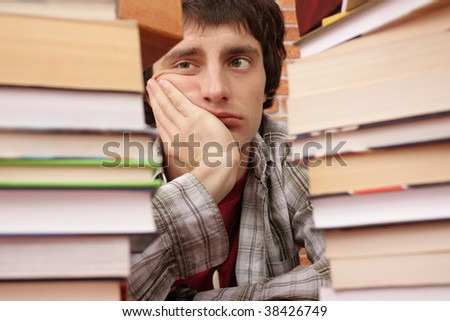 Student worried by number of books to read (man in focus) - stock photo