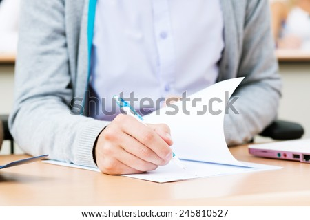 student writes a lecture in a classroom, close up without a face - stock photo