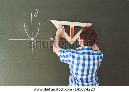 Student writing on the blackboard - stock photo