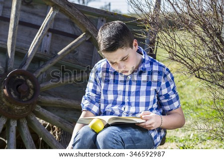 Student.Young man reading a book in outdoor with yellow apple. - stock photo
