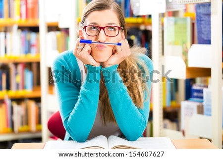 Student - young woman or girl sitting with books in library learning - stock photo