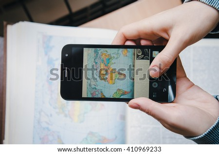 Student young woman taking a photo world map image book on screen black with Smartphone. Top view. Female hand holding and touch mobile phone in library textbook. Modern life concept. Film color - stock photo