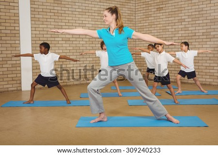 Students and teacher doing yoga pose at elementary school - stock photo