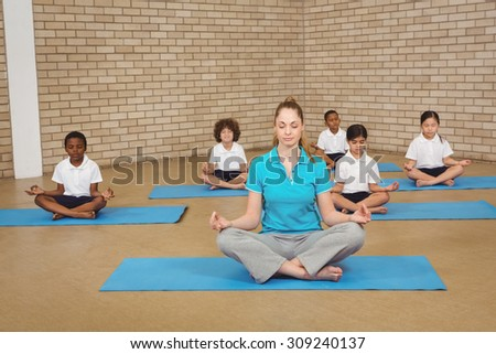 Students and teacher doing yoga pose at the elementary school - stock photo