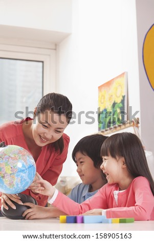 Students and teacher looking at globe - stock photo