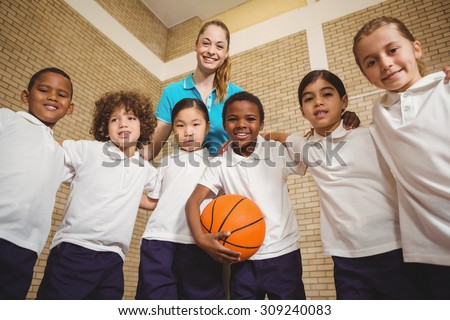 Students and teacher looking at the camera at the elementary school - stock photo
