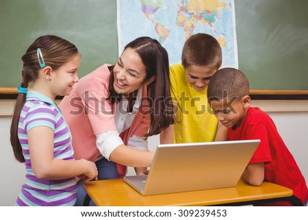 Students and teacher using a laptop at the elementary school - stock photo