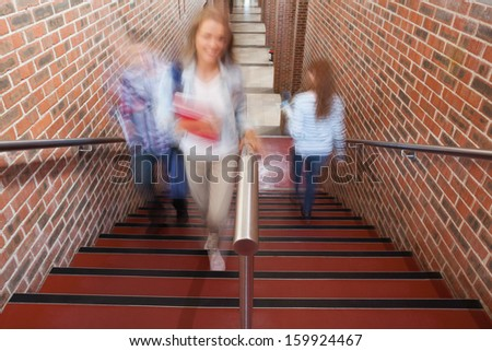 Students climbing stairs in school - stock photo