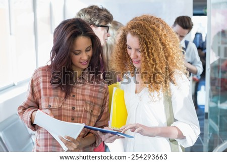 Students discussing their class notes at the college - stock photo
